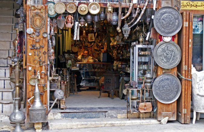 A vendor sits inside an antique shop in al-Jdeideh neighbourhood, in the Old City of Aleppo