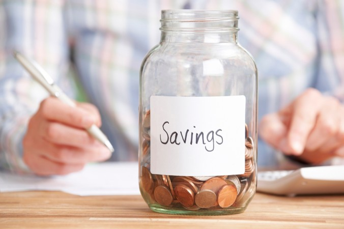 Woman Calculating Budget With Savings Jar In Foreground